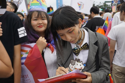 Taiwanese girl filling out a survey at Pride 2016